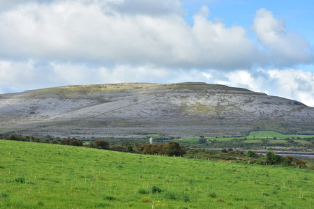 Karst landscape of Burren Plateau with fresh green pastures in foreground.