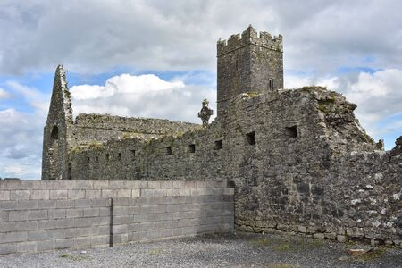 Stone ruins of medieval abbey of Clare with modern wall next to them.