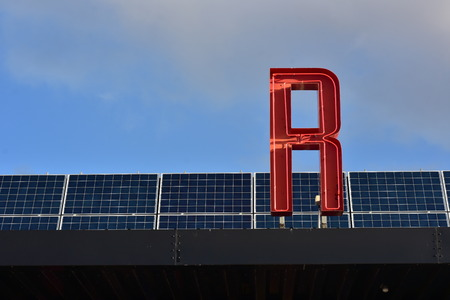 Red fluorescent tube sign letter on roof covered with solar panels. Banco de Imagens
