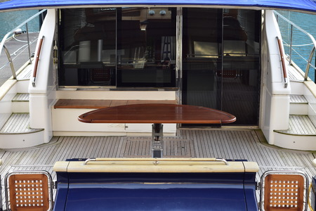 Wide stern deck with outdoor table and tinted glass door of large luxurious power catamaran. Stock fotó