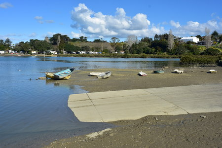 Small dinghies on mud flats next to concrete boat ramp in estuary at low tide. Stok Fotoğraf