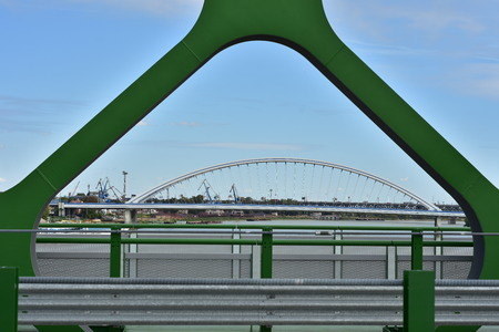 View of Apollo Bridge over river Danube through green painted steel arch of new Old Bridge.