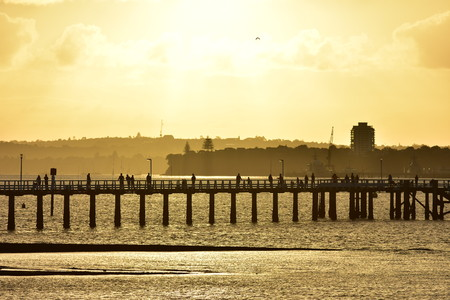Silhouettes of fishermen on Orakei wharf in Auckland in bright warm late evening light. Stock Photo