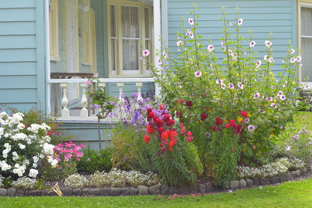 Colorful flowers in front of classic wooden villa porch.