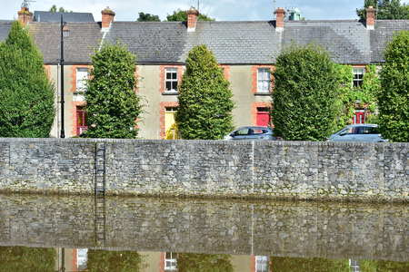 Row of typical narrow townhouses behind stone wall on bank of river Nore in Kilkenny. Stock Photo
