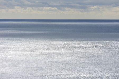 View of sea surface changing its color from silver to dark gray with lone tiny sailing ship being just small spot in vast ocean.