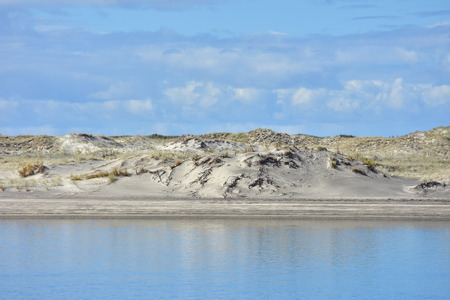 Layer of sand dune with recovering native vegetation in between blue sky and calm water surface reflecting skies.
