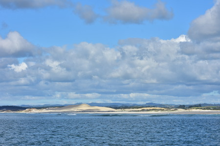Open coast with large sand dunes partially covered by native vegetation in Northland and partially cloudy but otherwise blue sky above.
