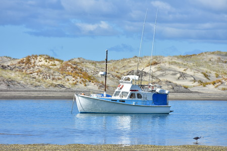 Motor launch moored in narrow harbor channel. Blue sky reflect on calm water surface creating layers contrasting with almost white sand dunes. Stock Photo