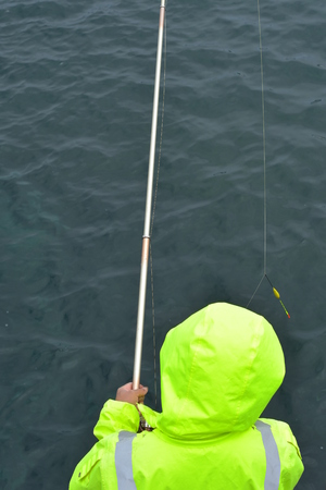 Fishing with metal rod and wearing modern fluorescent reflective synthetic oilskin jacket. Stock Photo