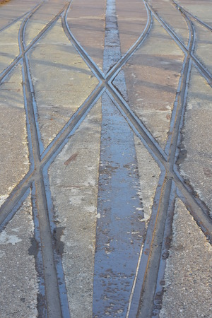 Unused interlaced tramway tracks with rusty and dented edges on paved road. Stock Photo