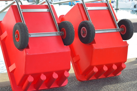 Red plastic box shaped industrial trolleys with one axle and galvanized metal frame and handle. Stock Photo