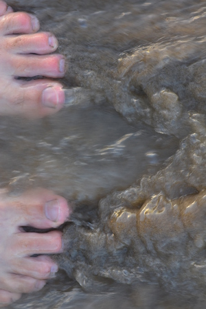 Water flowing over fine beach sand and human toes.