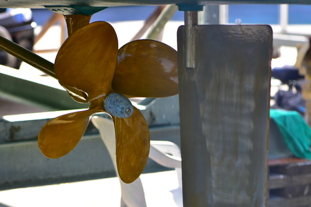 Freshly painted propeller with four blades and rudder under bottom of boat on hard stand.