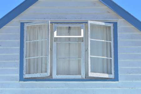Roof facade of traditional wooden house painted in white and blue with horizontal cladding and multi pane window. Stock Photo