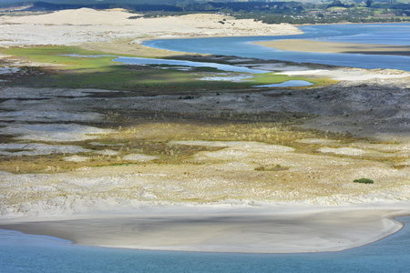Flat sandy coast with dunes of various colors covered with weeds stretching from open coast to enclosed harbor. Stock Photo