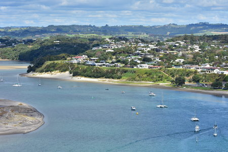 View of Mangawhai Harbour with moorings and sand dunes and dense housing of popular holiday destination of Mangawhai Heads.