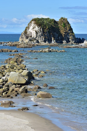 Vertical view of rocks stretching from shore to rocky islet near harbor mouth in Mangawhai Heads.