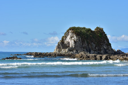 Rocky islet surrounded by flat reef bathing in oceanic surf near mouth of Mangawhai Harbour.