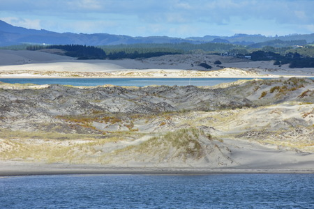 Sand dunes of various colors covered with native weeds forming barrier between harbor and open sea.