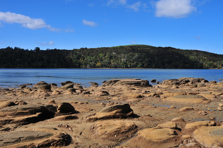 Very rugged volcanic coastal rocks exposed during low tide with deeper part of harbor in background. Stock Photo