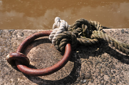 Thick rope tied to large thick rusty steel ring attached to concrete jetty.