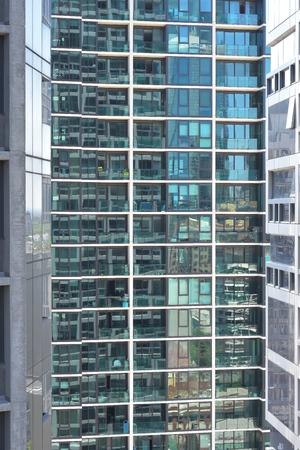 Glass exterior wall of tall apartment building with rows and columns of balconies and windows.
