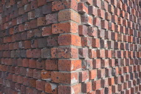 Corner detail of exterior wall of red bricks and mortar with bricks protruding form wall surface.