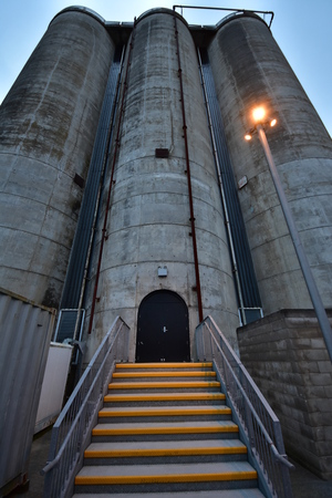 Industrial silo consisting of three tall concrete cylindrical towers interconnected by metal piping with staircase and gate at bottom of middle tower at night.