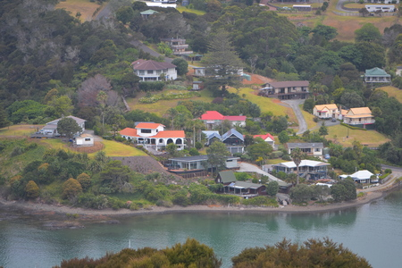 Wooden houses with yards and gravel access driveways along coast of harbor in Mangonui.