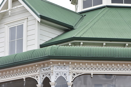 Detail of vintage white wooden villa with ornaments and corrugated sheet metal green painted roofs. Фото со стока