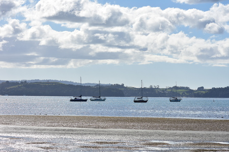 Shallow bay at low tide with sail boats on moorings and mud flats in foreground.