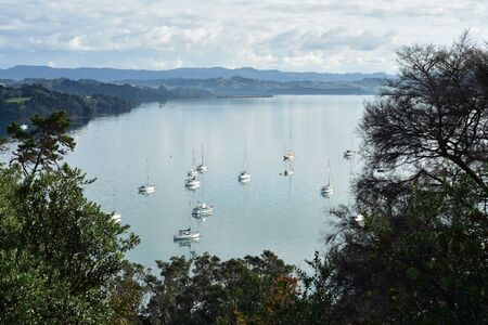 Moored boats floating on absolutely calm surface of Mahurangi Harbour near Scotts Landing with hilly country of Rodney District in background. Stock Photo