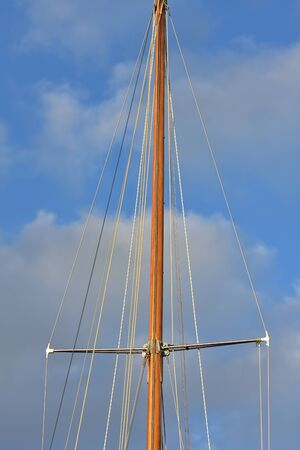Wooden mast of classic yacht with shrouds supported by spreaders and forestay/backstay and halyards.