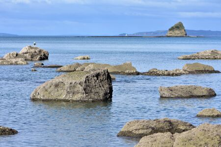 Rocks protruding from calm sea surface with islet and rocky reef in background. 版權商用圖片