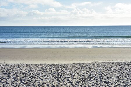 Oceanic beach sand of creamy color with areas smoothed by tidal water movement.