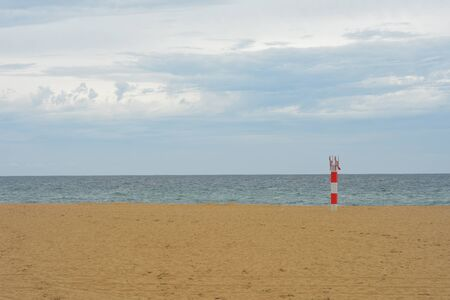 White and red metal pole with No Dogs sign on sandy ocean beach with sea and horizon in background. Stock fotó