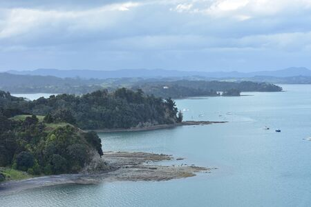Tiny bays and peninsulas with rocky reefs and platforms exposed at low tide and moored recreational vessels in Mahurangi Harbour near Auckland in New Zealand. Stock fotó
