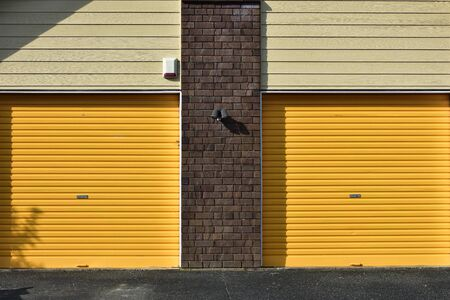 Yellow metal garage gates with brick wall between them and weatherboard cladding above. Stock fotó