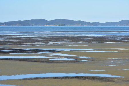 Sand flats with shallow pools in Snells Beach at low tide with Kawau Island in background. Stock fotó