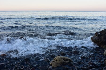 Mild surf on beach of black volcanic pebbles in eastern Bali.