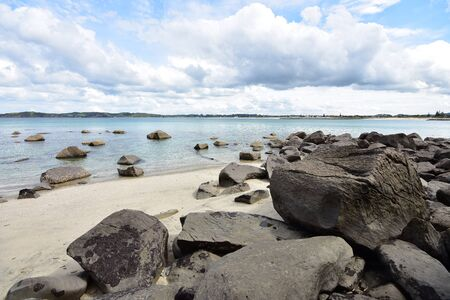 Sandy beach with large stones both on shore and in clear shallow water.