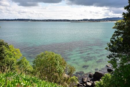 Calm clear water at mouth of Whangateau Harbour viewed from Ti Point. Stock fotó