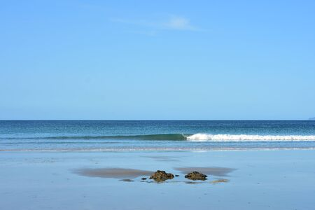 Flat sandy shore at low tide with two rocks protruding from smooth sand and tiny surf wave on calm ocean.