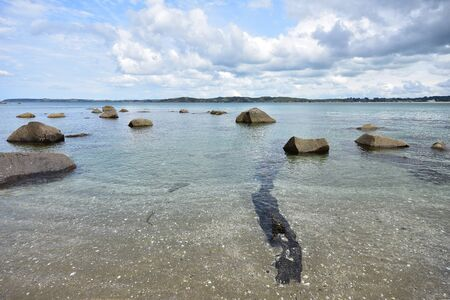 Shallow sandy shore with clear water and large stones near Ti Point in New Zealand.