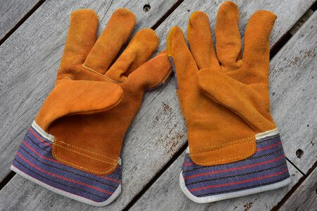 Pair of work gloves made from cheap leather with textile extensions around wrists.