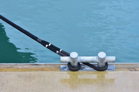 Metal cleat for heavy vessels on jetty with dark synthetic line tied. Stock fotó