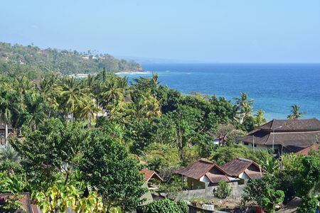 Rural coast of eastern Bali with coastal homes turned holiday resorts and dense tropical vegetation.