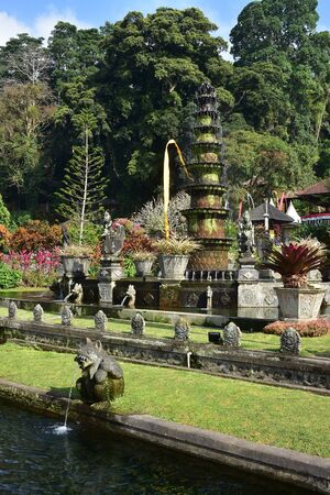 Ornamental garden terraces with stone statues and fountain in Tirtagangga Water Palace in Bali. Imagens