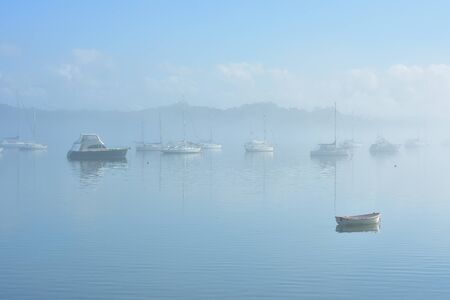 Power and sail boats anchored in flat calm harbor appearing from morning fog.